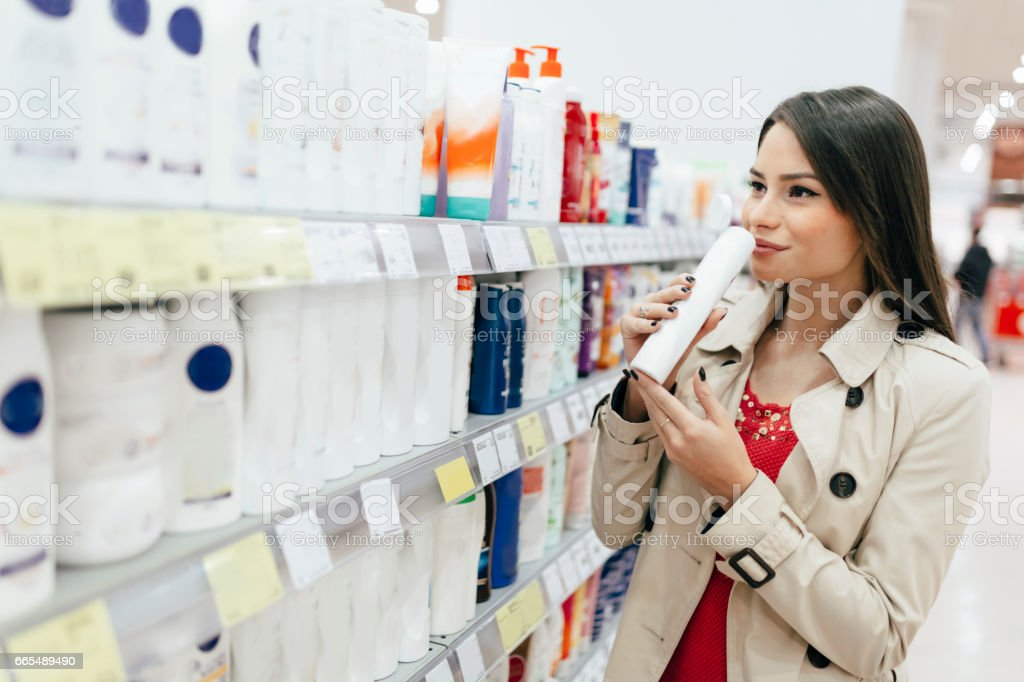 Beautiful woman buying body care products in supermarket stock photo