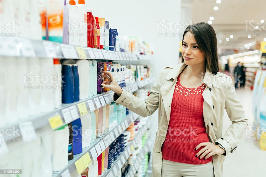 Beautiful woman buying body care products stock photo