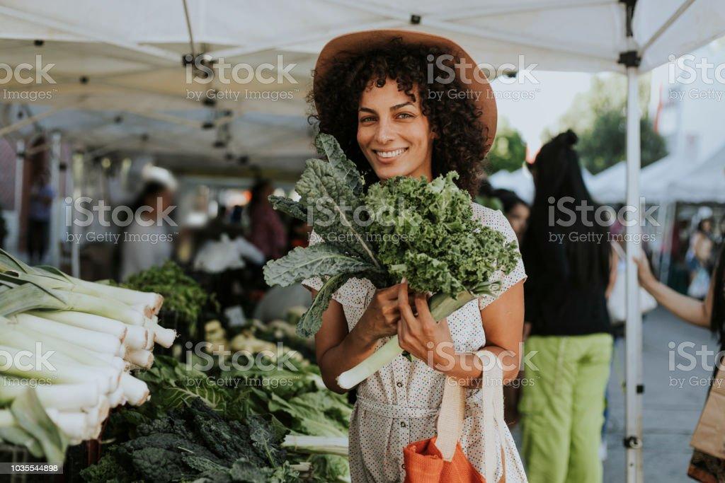 Schöne Frau kaufen Grünkohl auf einem Bauernmarkt - Lizenzfrei Aussuchen Stock-Foto