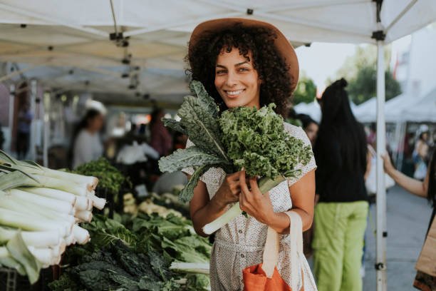 beautiful woman buying kale at a farmers market - organic stock pictures, royalty-free photos & images