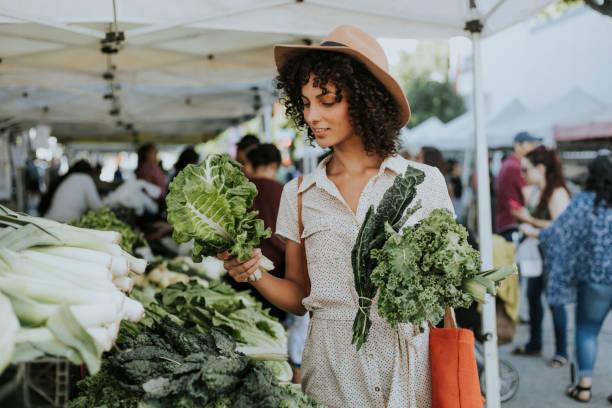 Beautiful woman buying kale at a farmers market stock photo