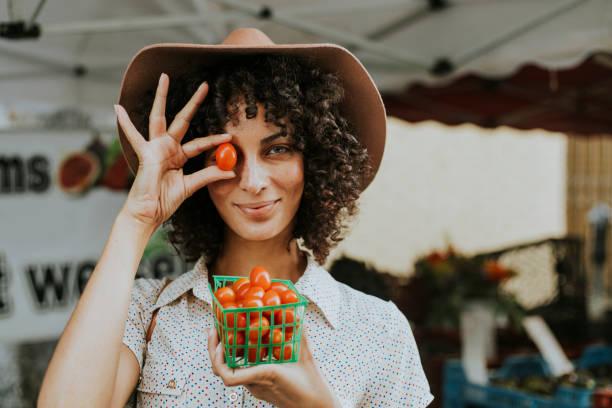 美しい女性の農民市場でトマトを購入 - ビーガン ストックフォトと画像