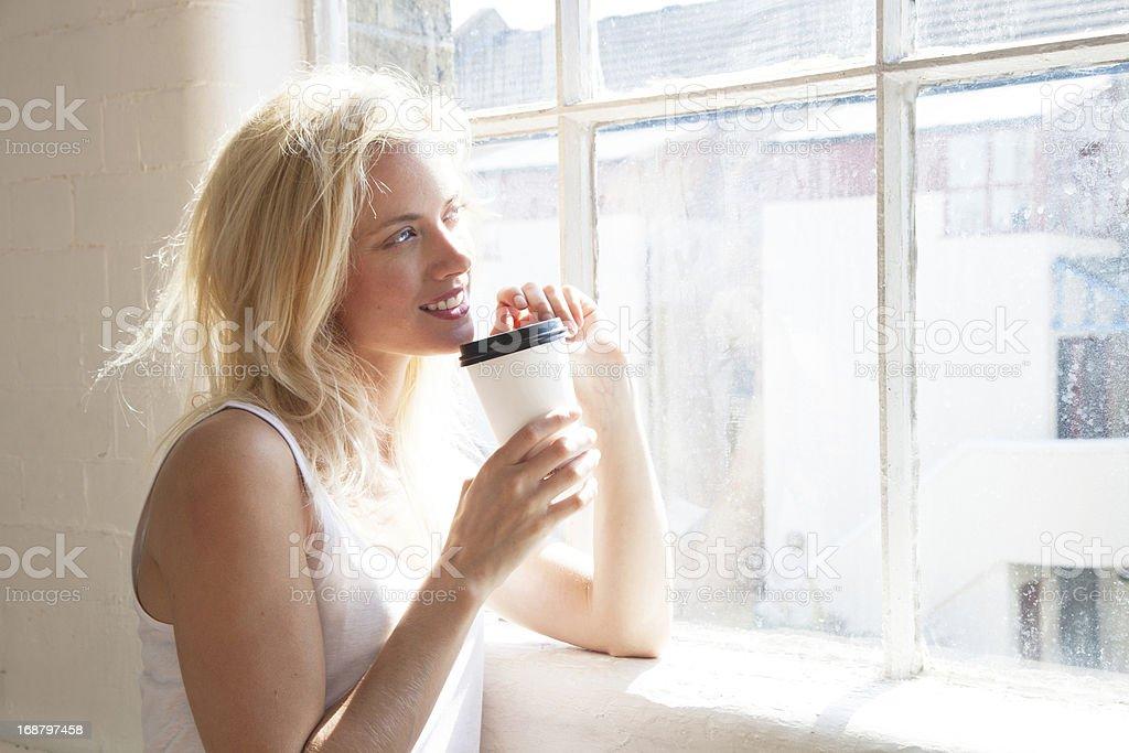 Beautiful woman by window with takeaway coffee royalty-free stock photo