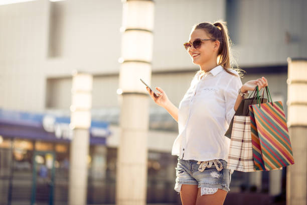 schöne frau mit einkaufstüten taxi rufen - besondere geschenke stock-fotos und bilder