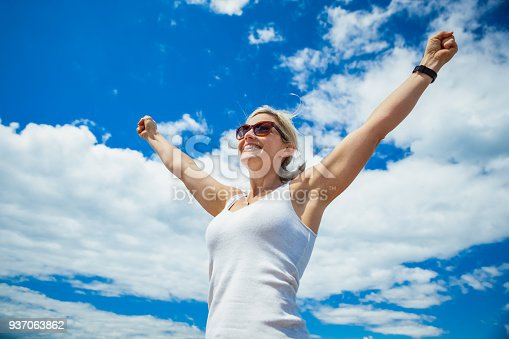 istock Beautiful Woman Carefree in Blue Sky 937063862