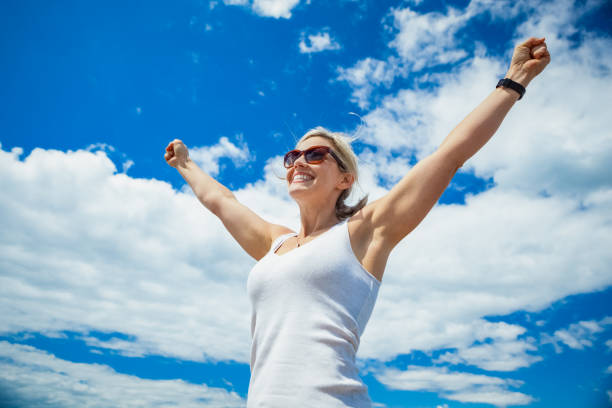 beautiful woman carefree in blue sky - summer background стоковые фото и изображения