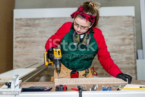 istock Beautiful woman carpenter drilling wooden plank, carpentry 984942478