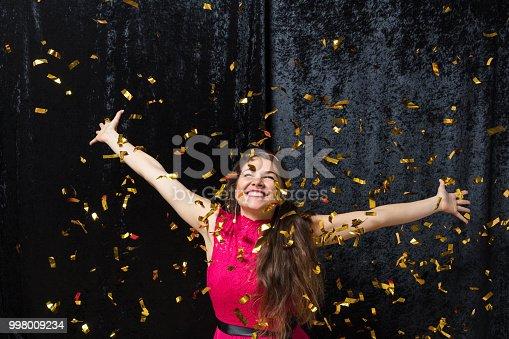 istock Beautiful woman celebrating with glitter 998009234