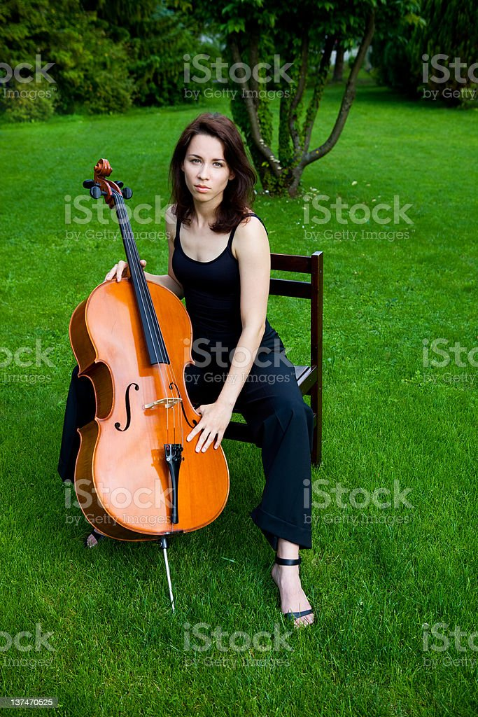 Beautiful woman cellist playing cello outdoors stock photo