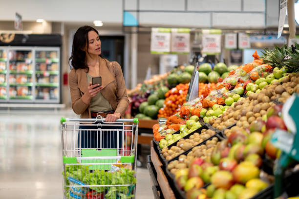 Beautiful woman checking a shopping list on smartphone while looking for fruits on the vegetable display of a supermarket Beautiful woman checking a shopping list on smartphone while looking for fruits on the vegetable display of a supermarket and pushing a cart produce aisle stock pictures, royalty-free photos & images