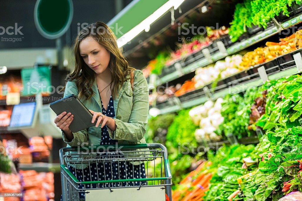 Beautiful woman checks tablet while shopping stock photo