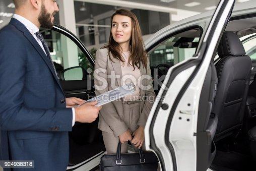 1049198210 istock photo Beautiful Woman Choosing New Car 924938318