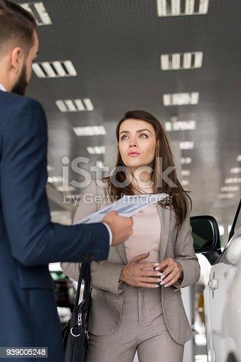 1049198210 istock photo Beautiful Woman Choosing New Car 939005248