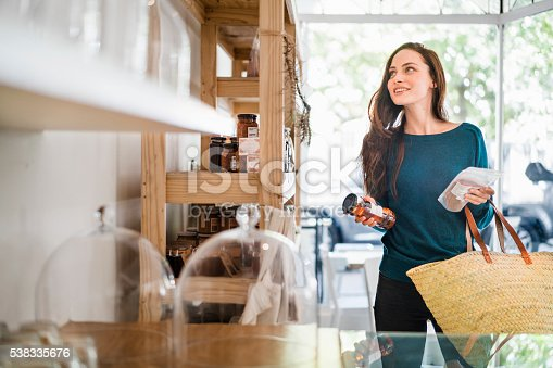 A photo of happy young woman holding bag and products in coffee shop. Beautiful female is choosing packets from shelves. She is shopping in store.