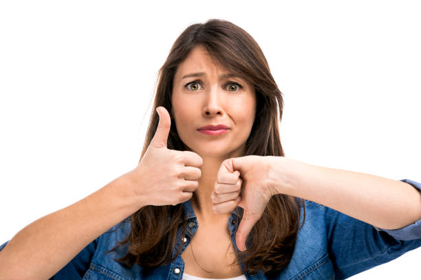 beautiful woman confused making thumbs up and down - thumbs down stock photos and pictures