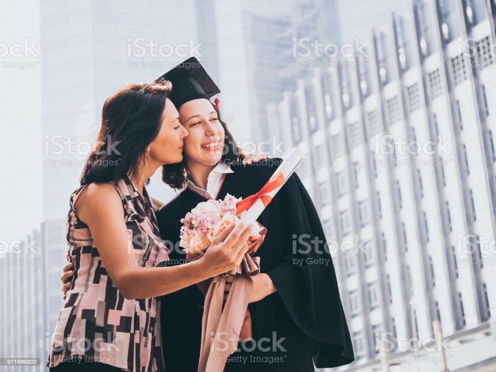 Hermosa mujer felicita a su hija en día de la graduación, concepto - foto de stock