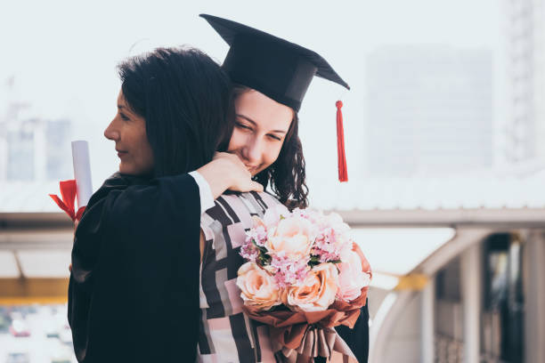 Beautiful woman congratulates for her daughter on graduation day, Successful concept stock photo