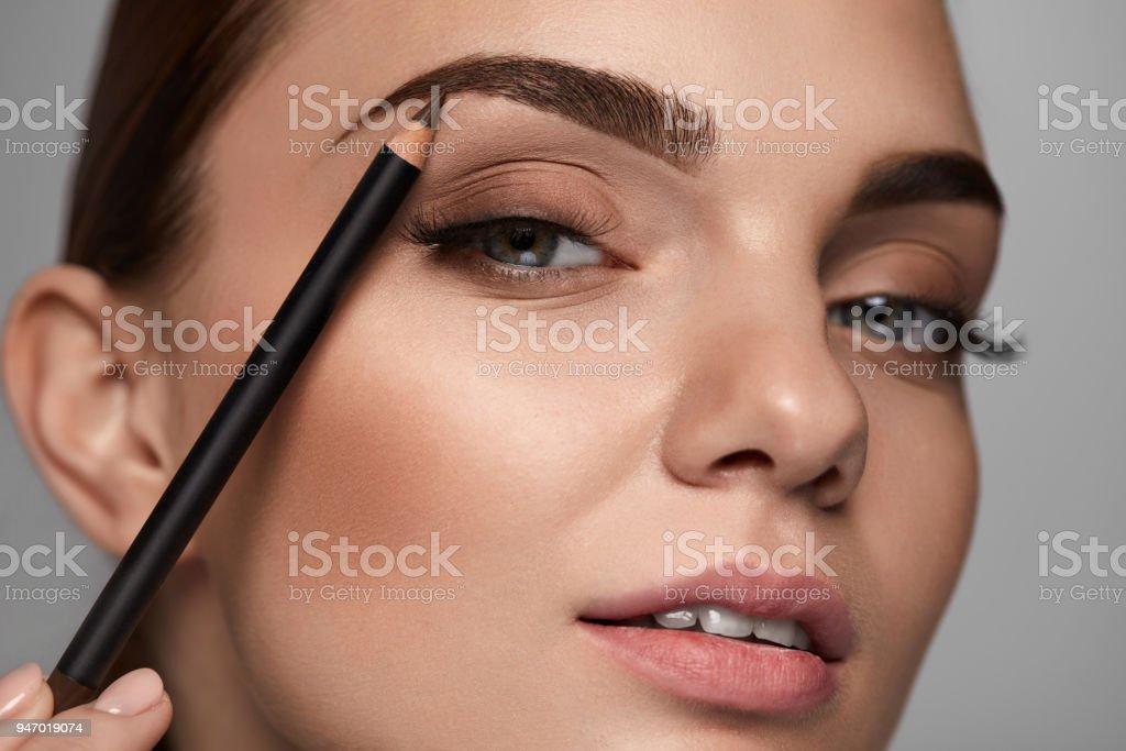 Belle femme, remodelage des sourcils avec un crayon. Beauté photo libre de droits