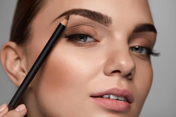 Belle femme, remodelage des sourcils avec un crayon. Beauté - Photo