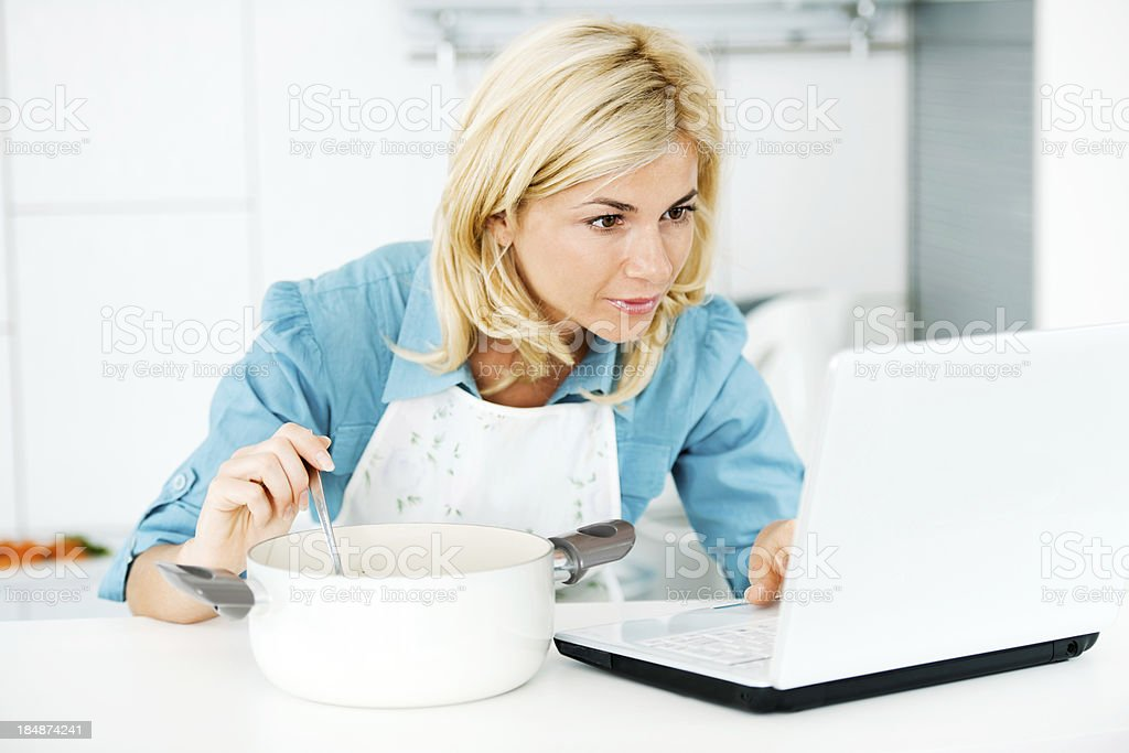 Beautiful woman cooking and looking for a recipe online. royalty-free stock photo