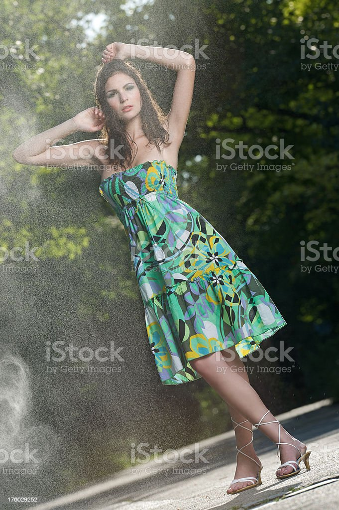 Beautiful woman cooling off in drizzling summer rain (XXXL) royalty-free stock photo