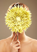 Close-up of a young beautiful woman naked covering her face with a green sun flower.  Vertical shot.
