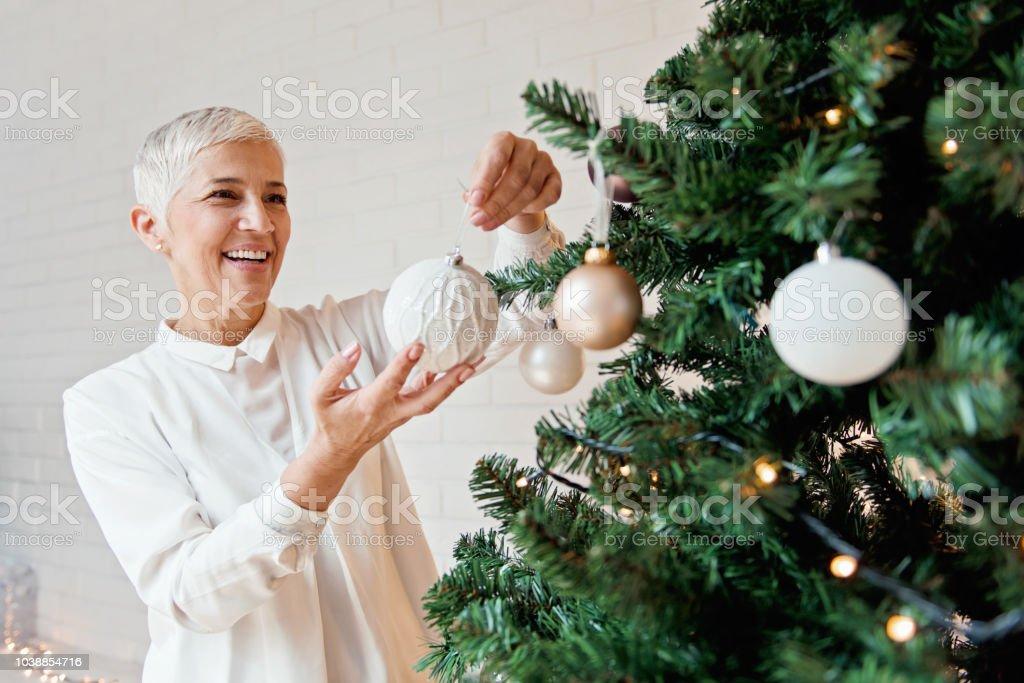 Beautiful woman decorating a Christmas tree stock photo