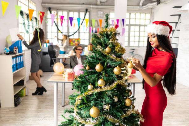 schöne frau schmücken weihnachtsbaum am arbeitsplatz - frohes neues jahr stock-fotos und bilder