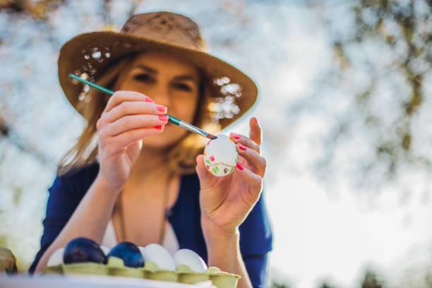 schöne frau, die deko-ostereier im garten für urlaub - schöne osterbilder stock-fotos und bilder
