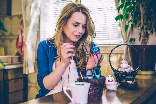schöne frau, die deko-ostereier mit decoupage-technik für feiertage - schöne osterbilder stock-fotos und bilder