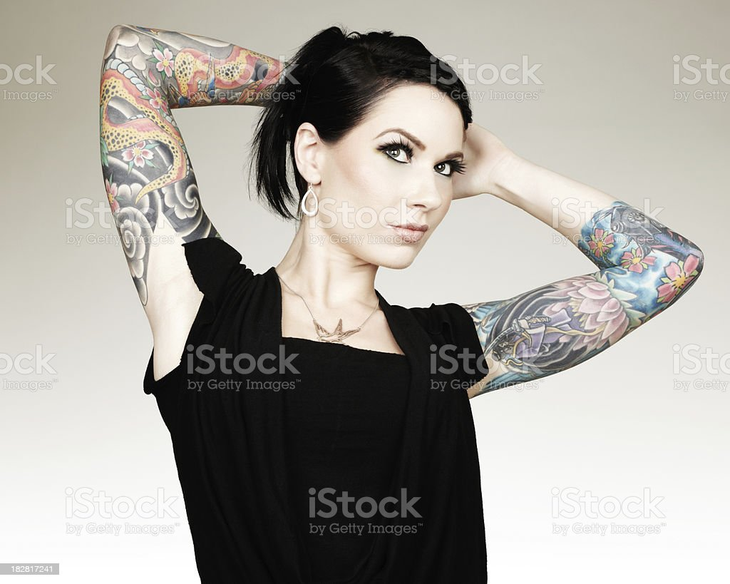 sch ne frau zeigt ihr armsleeve tattoos w hrend l chelnd. Black Bedroom Furniture Sets. Home Design Ideas
