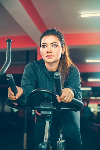 Beautiful woman does cardio exercise on air bike in gymnasium. stock photo