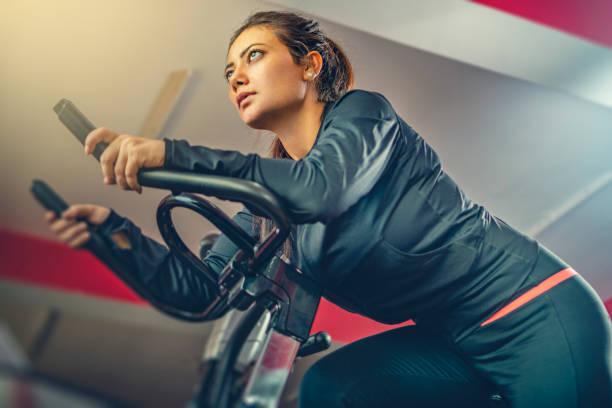 Schöne Frau macht Cardio-Übung auf dem Airbike in der Turnhalle. – Foto