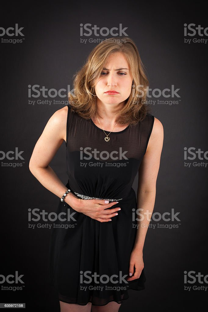 Beautiful woman doing different expressions in different sets of clothes: stomachache stock photo