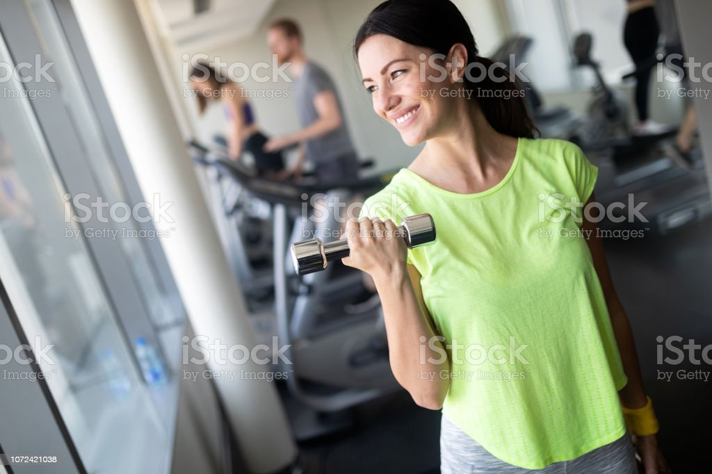 Young beautiful woman doing exercises with dumbbell in gym. Glad...