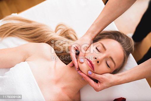 istock Beautiful woman doing facial massage in a spa salon. 1179339106