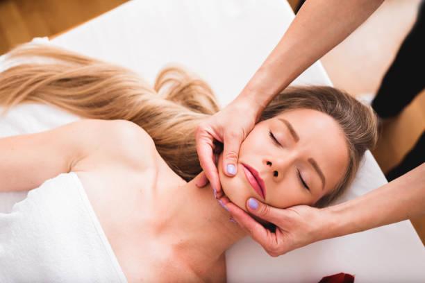 Beautiful woman doing facial massage in a spa salon. stock photo