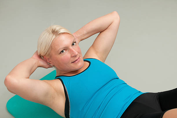 Beautiful woman doing sit-ups at the gym stock photo