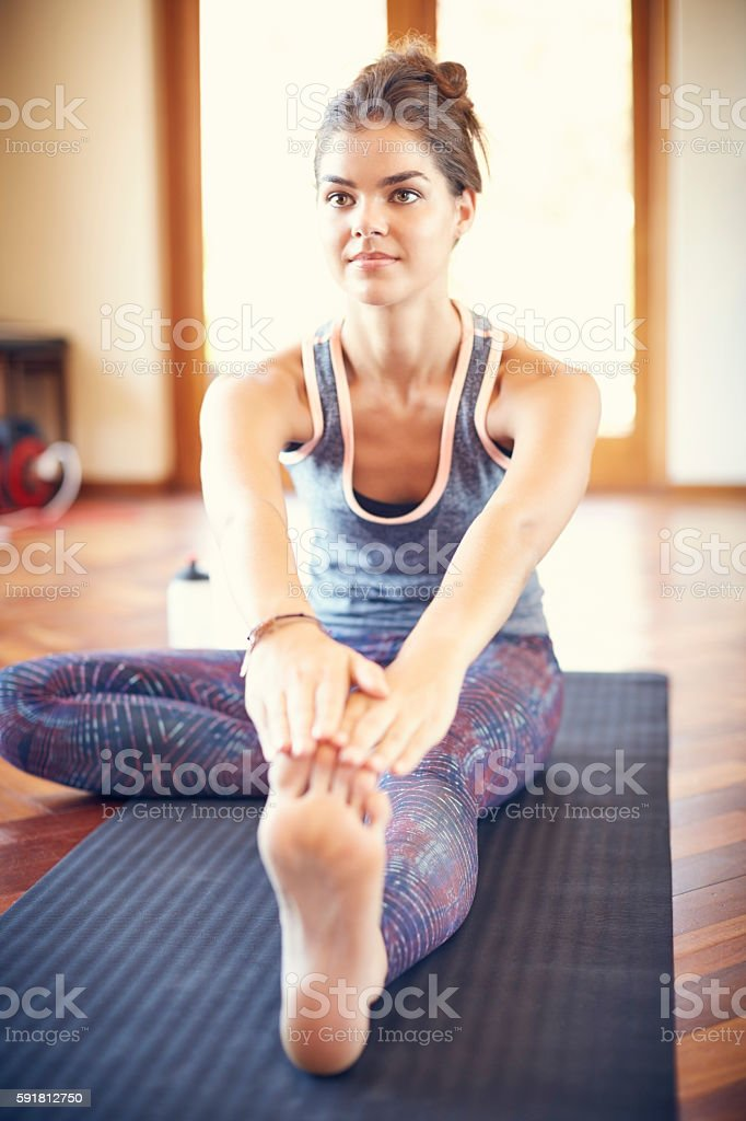 Beautiful woman doing stretching exercise on yoga mat at home stock photo