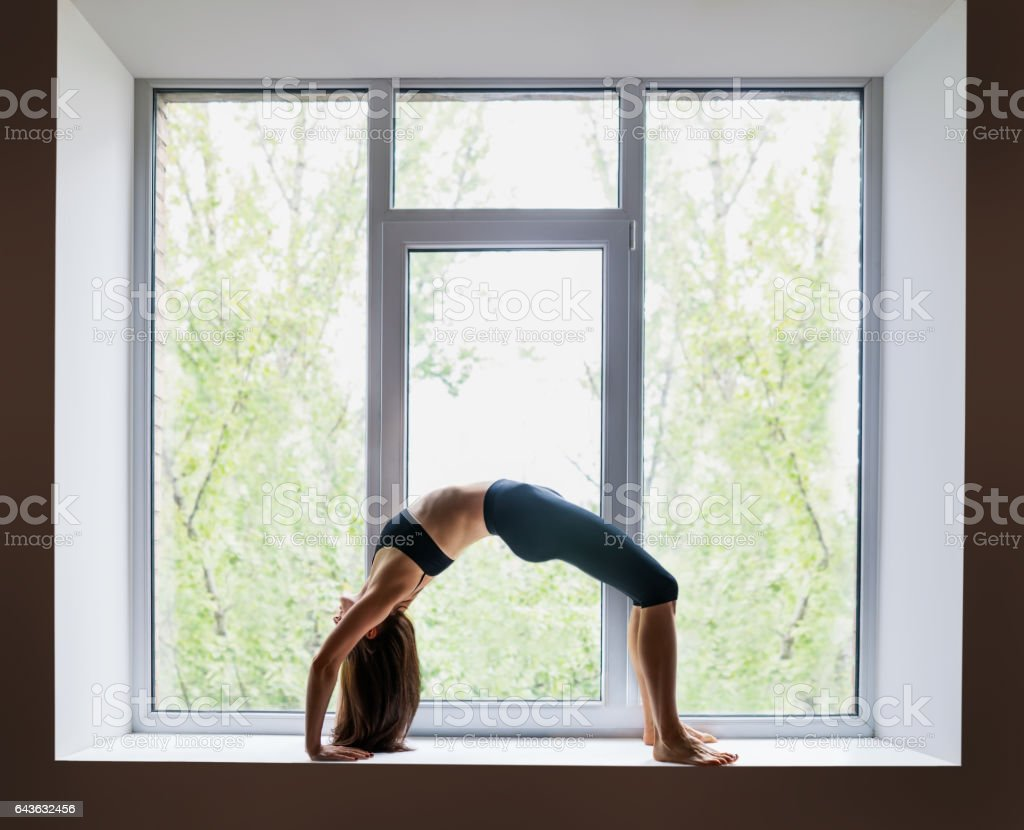 Bella mujer haciendo yoga asana postura arco hacia arriba (la rueda) en el  alféizar 0892da9459db