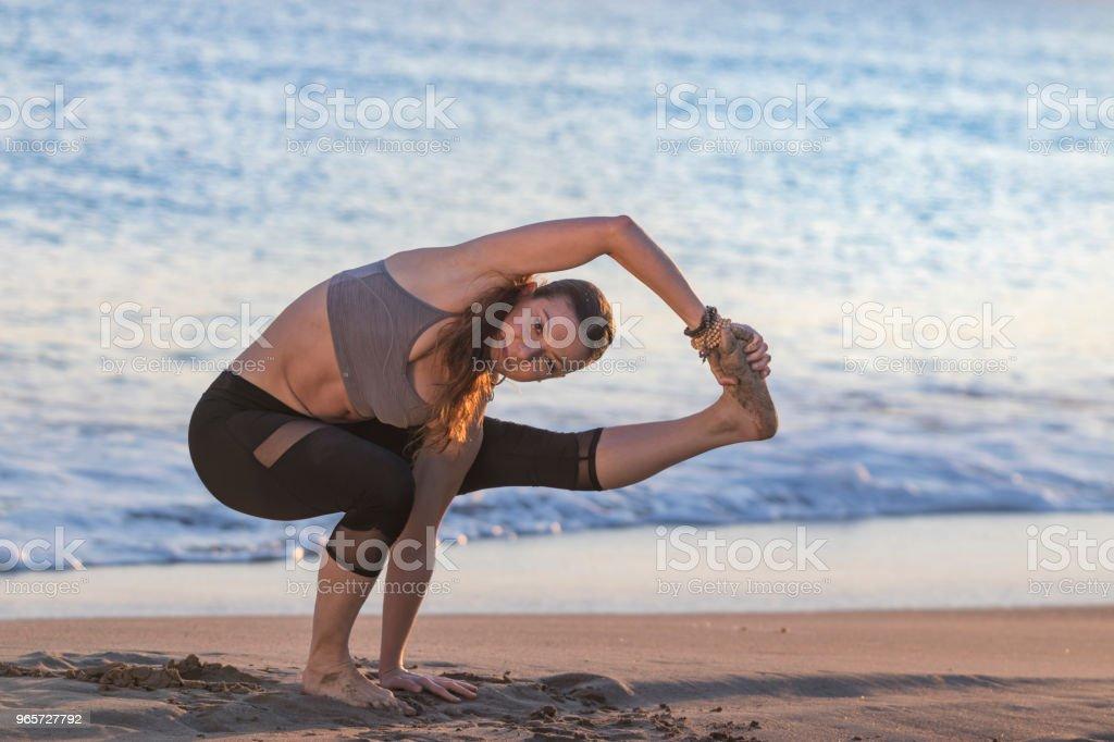 Beautiful woman doing yoga at the beach at sunset - Royalty-free Activity Stock Photo