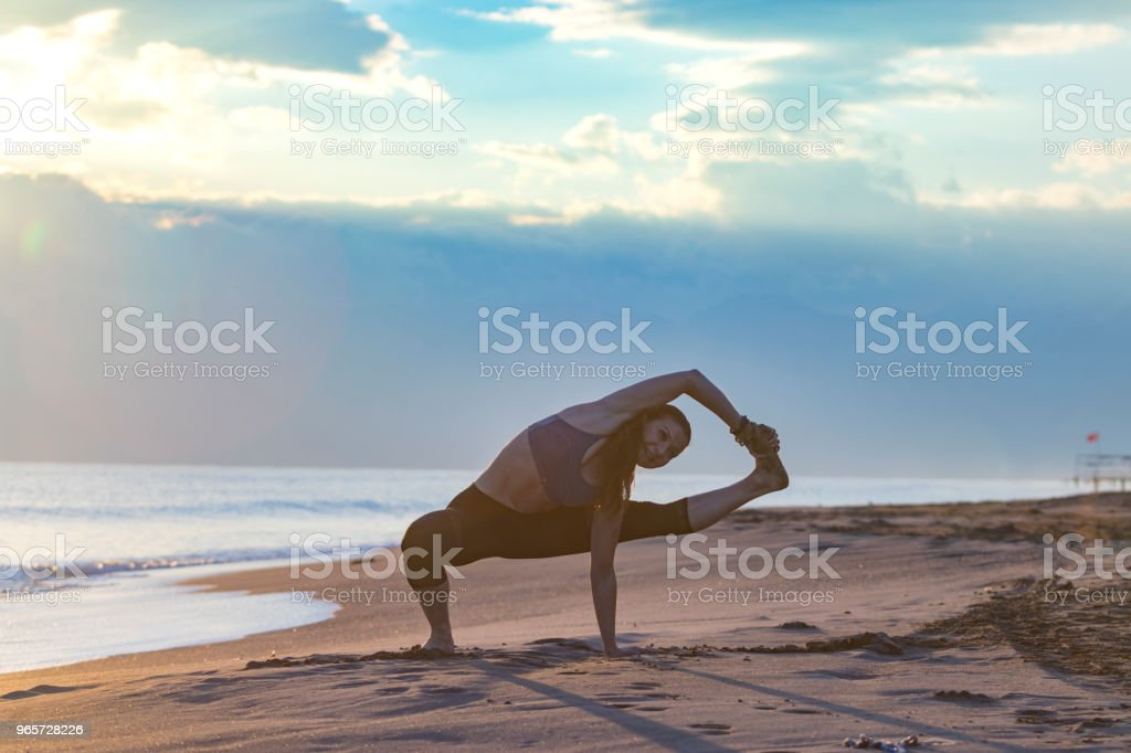 Beautiful woman doing yoga at the beach at sunset - Royalty-free Adulto Foto de stock
