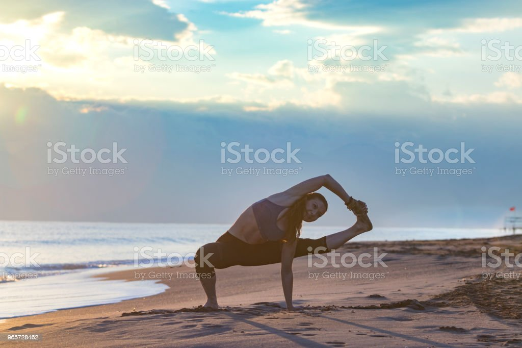 Beautiful woman doing yoga at the beach at sunset - Royalty-free Activity Stock Photo