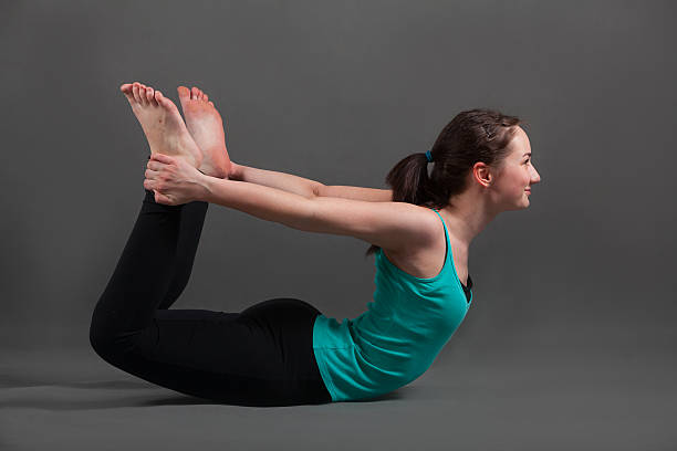 beautiful woman doing yoga dhanurasana stock photo