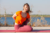 beautiful woman doing yoga on green grass in park at summer morning.
