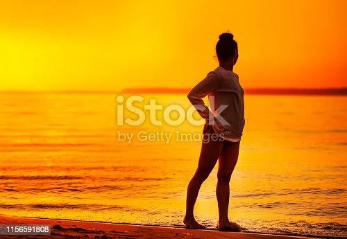 beautiful woman doing yoga on the beach at sunset