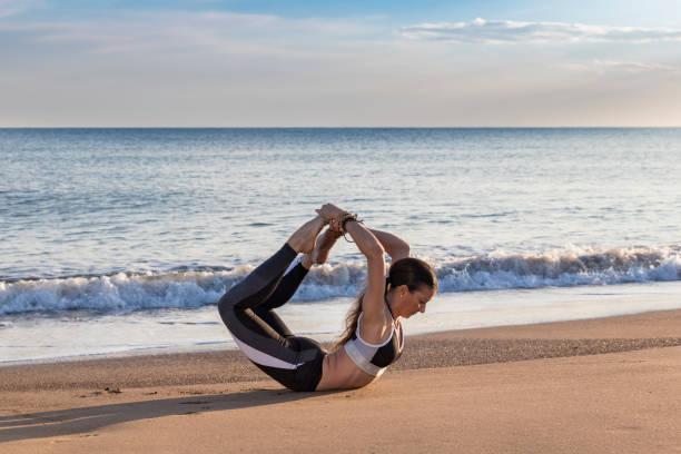 sahilde, dhanurasana yoga yaparken güzel kadın. - serpilguler stok fotoğraflar ve resimler