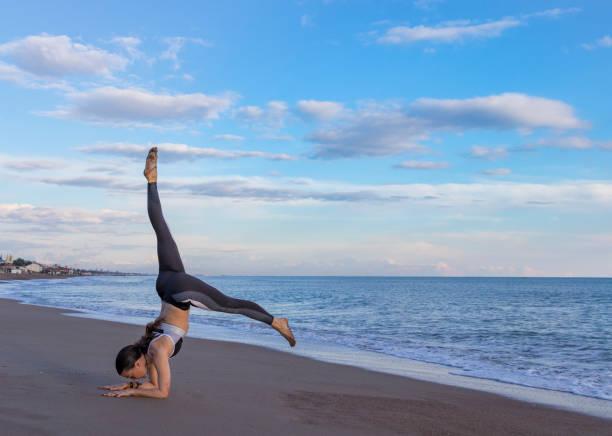 kumsalda yoga yaparken güzel kadın - serpilguler stok fotoğraflar ve resimler