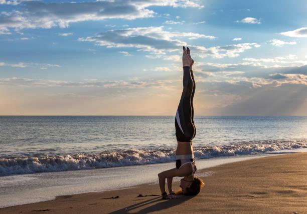 sahilde, sirsasana yoga yaparken güzel kadın. - serpilguler stok fotoğraflar ve resimler