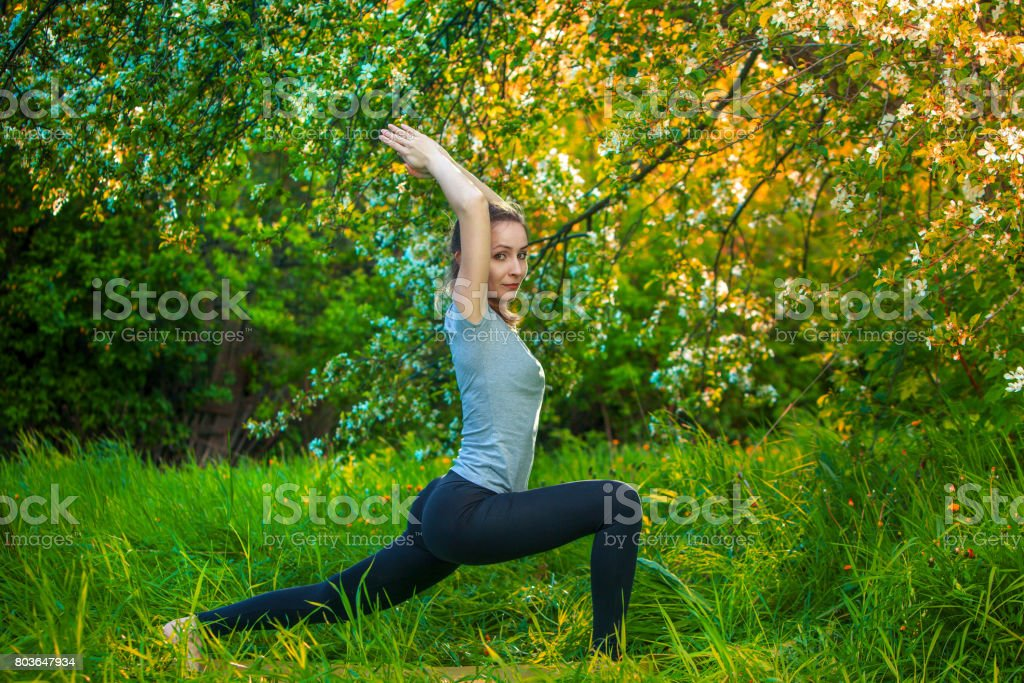 beautiful woman doing yoga outdoors On green grass stock photo